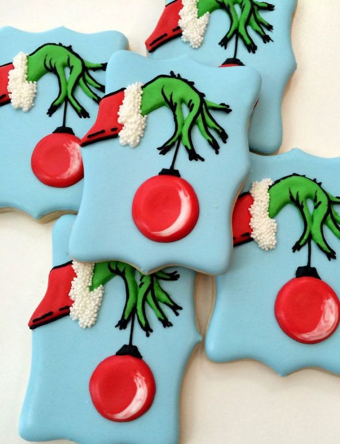 grinch cookies, decorated with blue red and green icing, the grinch's hand holding an ornament, how to make icing for cookies
