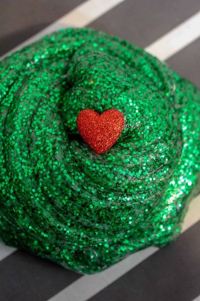 grinch slime made of green glitter, christmas craft ideas for kids, red glittery heart on top