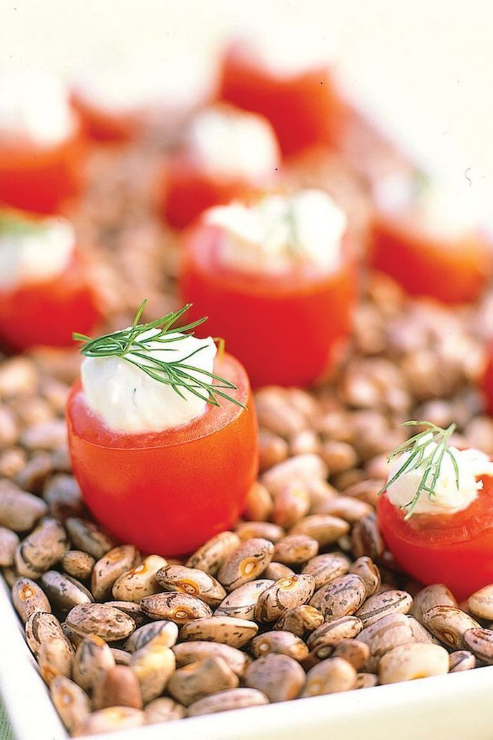 halved cherry tomatoes, sour cream inside and dill on top, christmas party finger foods, placed on bowl full of beans