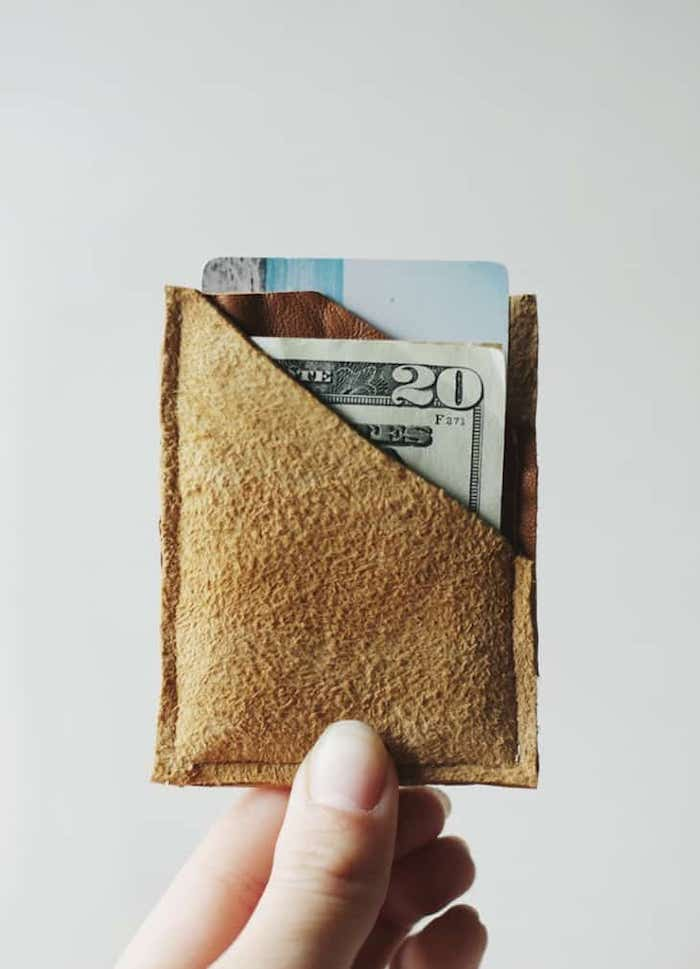 hand holding small brown leather, money and cards inside, christmas gifts for men, white background