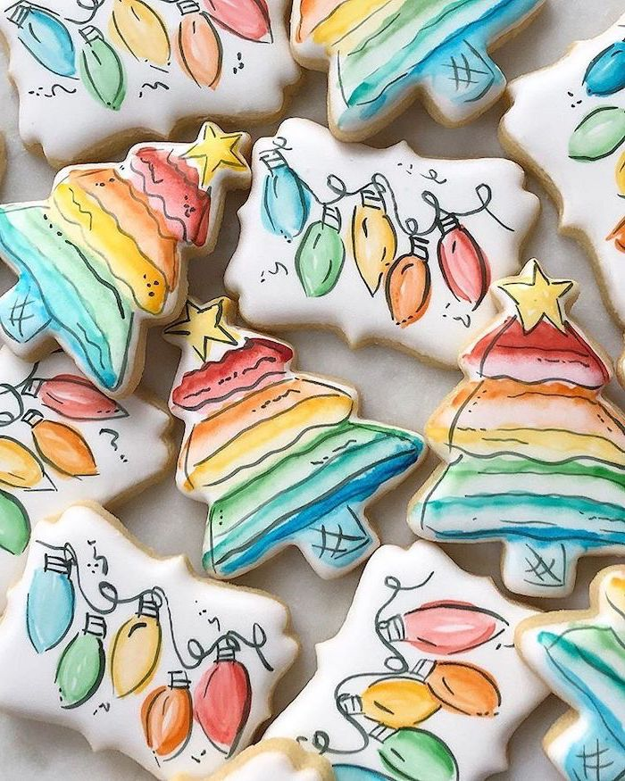 christmas tree shaped cookies, how to make icing for cookies, hand painted as trees and hanging lights, placed on white surface
