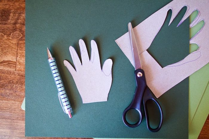 handprint cut out of green paper, homemade christmas crafts, step by step diy tutorial, pen and scissors