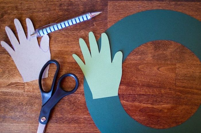 pen and scissors, handprint cut out of green paper, homemade christmas crafts, placed on wooden surface