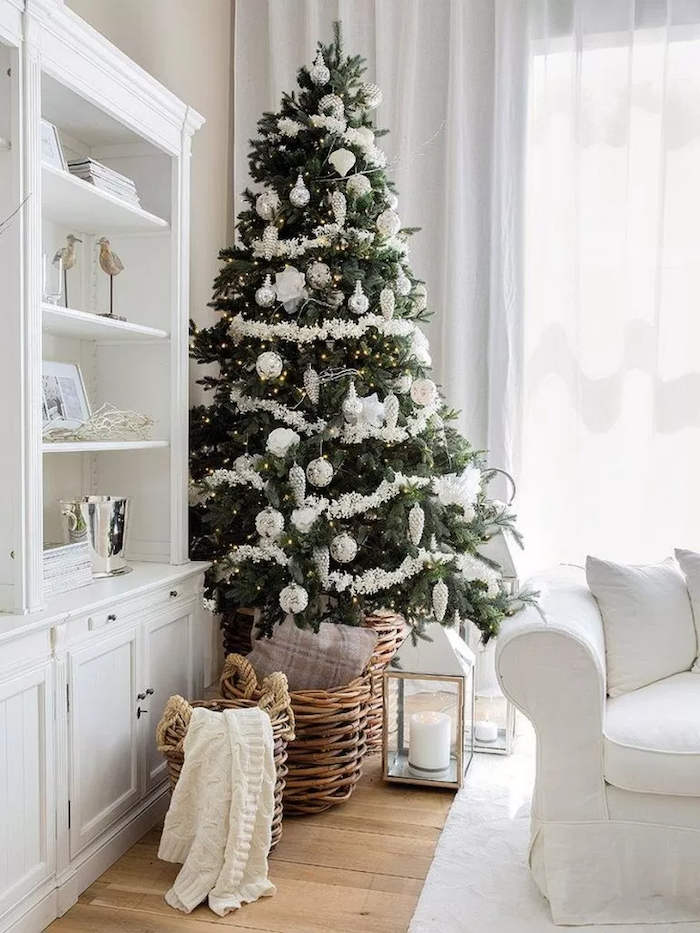 tall tree decorated with white garland, white and silver ornaments, beautiful christmas trees, placed in wooden basket