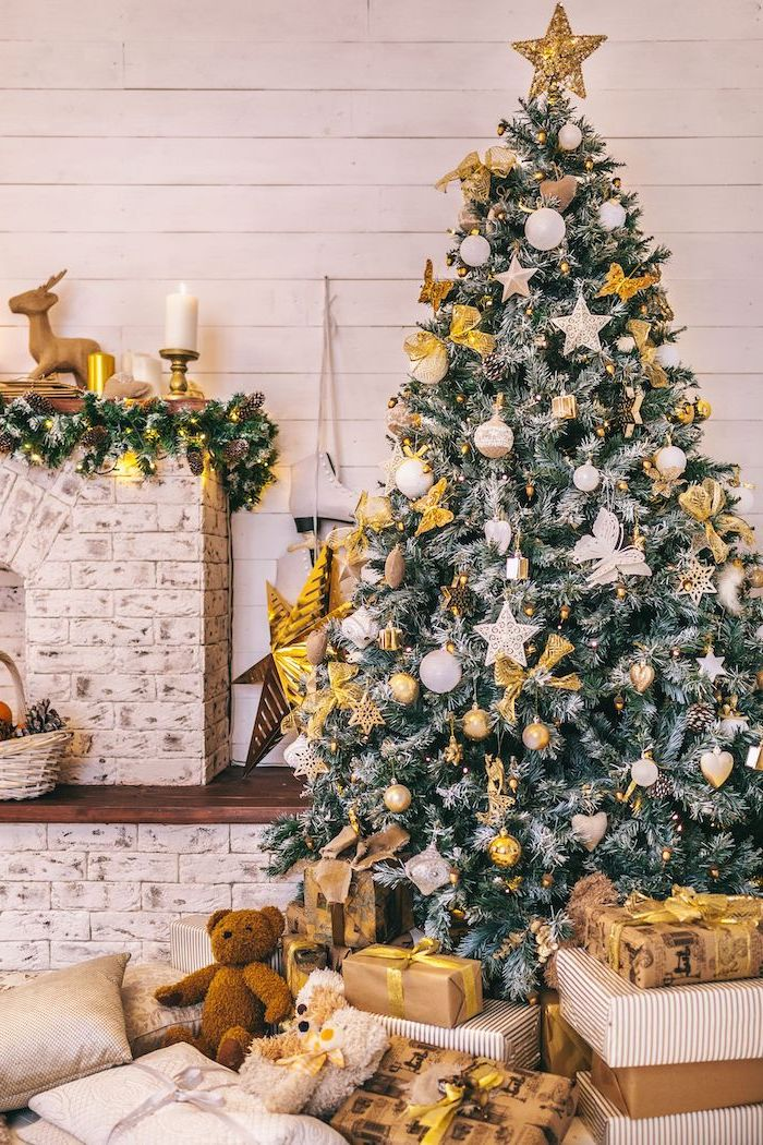 tall tree decorated with gold bows, white and silver ornaments, beautiful christmas trees, gold star topper
