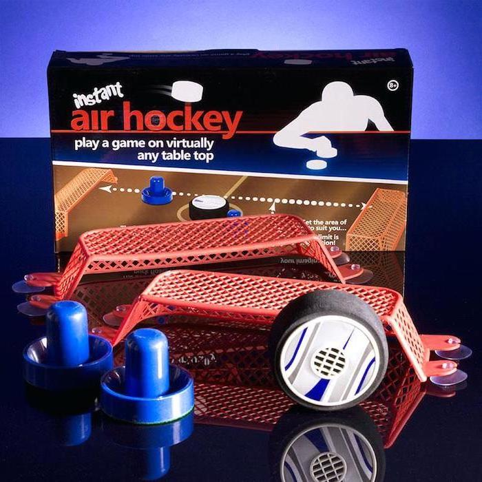 instant air hockey game, christmas gift ideas for boyfriend, pucks and goal posts, placed on black surface