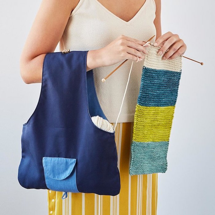 woman holding a knitting bag, wearing white top and yellow skirt, knitting a colorful scarf, christmas gifts for mothers