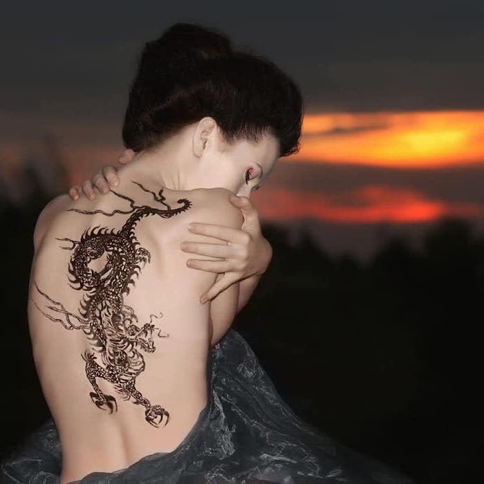 large back tattoo, on woman with black hair, wearing black tulle dress, dragon sleeve tattoo, sunset in the background