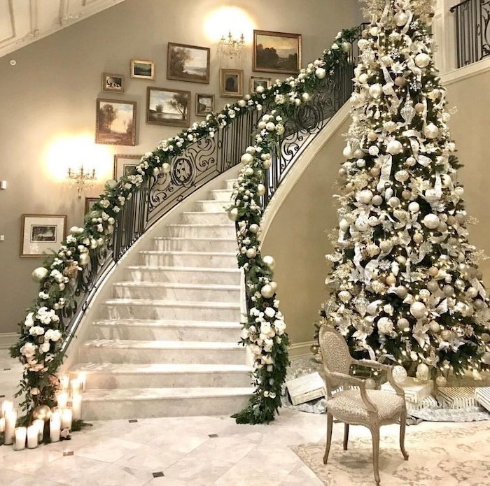 tall tree next to a large staircase, decorating christmas tree with ribbon, decorated with white and silver ornaments and flowers