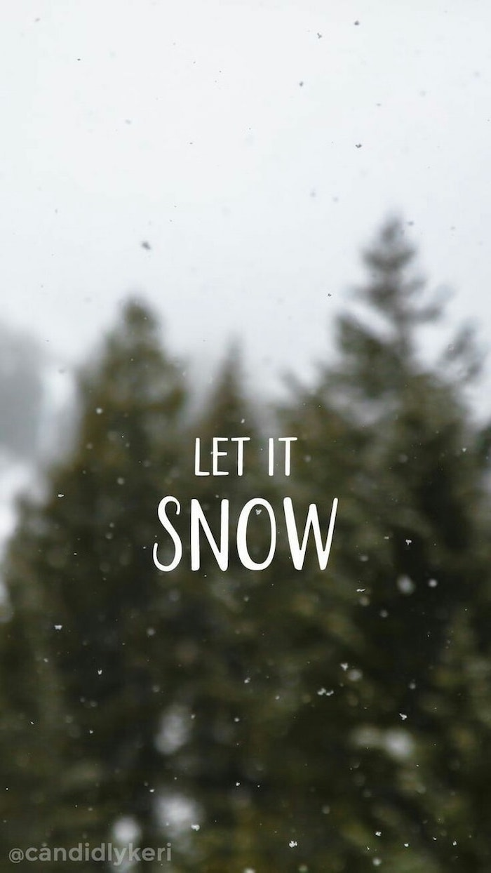 let it snow written over blurred background, tall trees and snow falling, screen saver wallpaper
