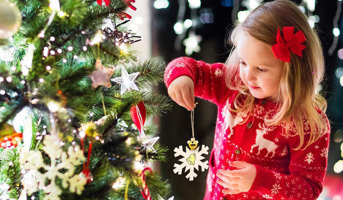 diy christmas ornaments for kids, little girl holding a handmade paper snowflake, next to a decorated christmas tree