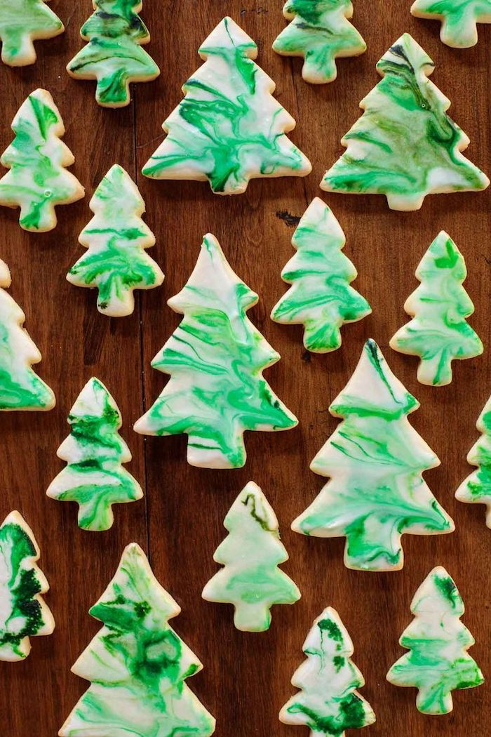 christmas tree shapes cookies, placed on wooden surface, christmas cookie decorating ideas, white and green icing on top