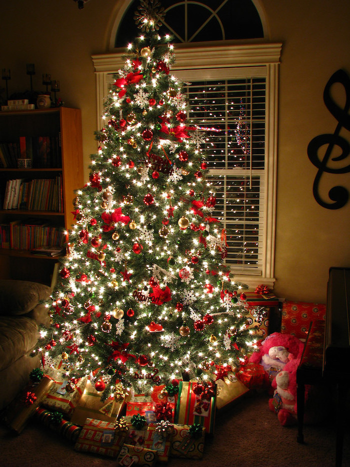 tree decorated with lots of lights, red and gold ornaments and bows, decorating christmas tree with ribbon, presents underneath