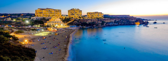 north golden bay in malta, large hotels on the seaside on top of large rocks, beautiful beaches, photo taken at sunset