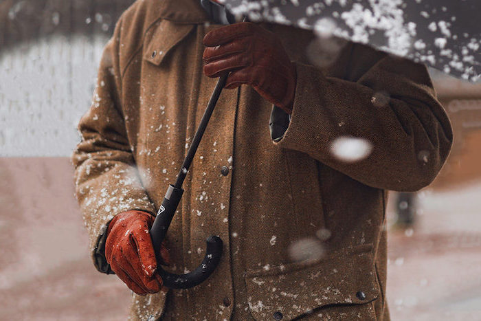 man holding a black umbrella, wearing brown coat and brown leather gloves, christmas gift ideas for boyfriend, snow falling