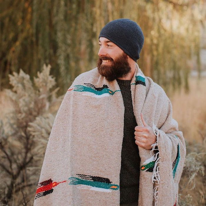 man with beard smiling, wrapped in a large cozy blanket, wearing black sweater and blue beanie, unique gifts for men