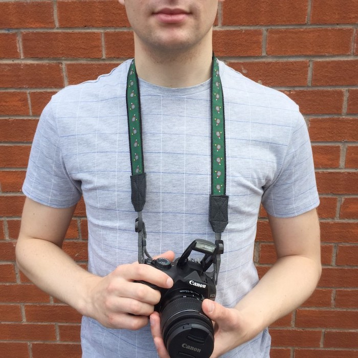 man holding a canon photo camera with green strap, step by step diy tutorial, wearing grey shirt, gift ideas for men, brick wall in the background