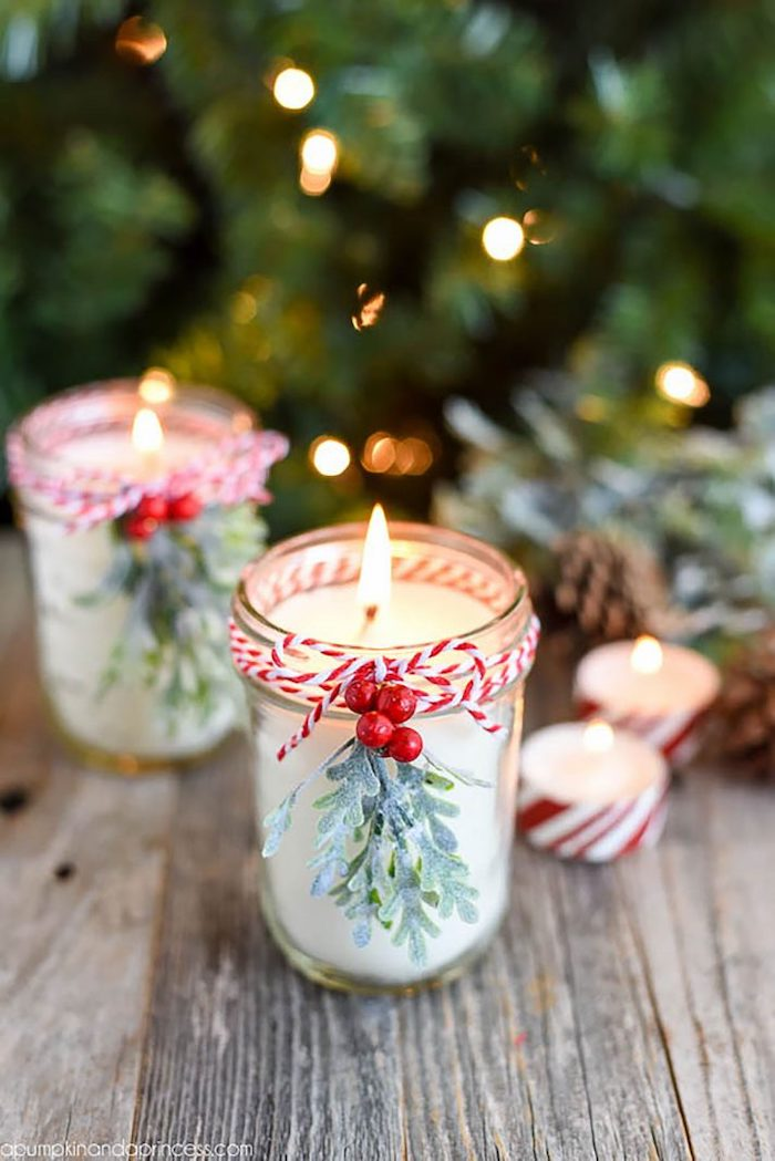 mason jars with candles inside, decorated with mistletoe branches and cranberries, what to get mom for christmas\