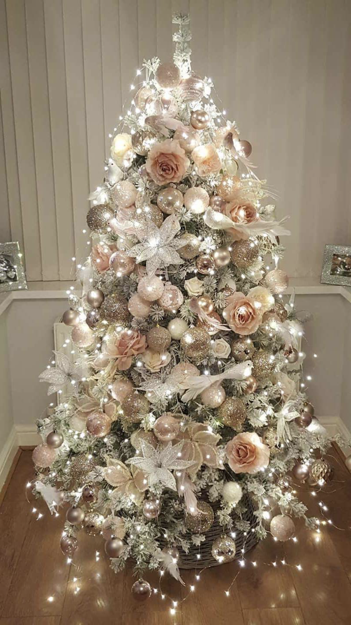 white christmas tree decor, rose gold and silver ornaments, faux flowers and lots of lights on a tree, placed on wooden floor