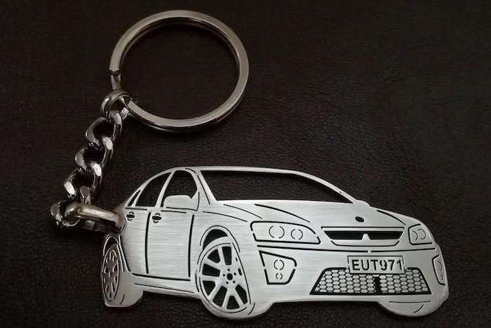 metal keyring, personalised with the owner's car and plate number, unique gifts for men, placed on black leather surface
