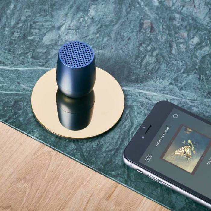 blue mini wireless speaker, placed on golden coaster, next to a phone playing music, good gifts for boyfriend