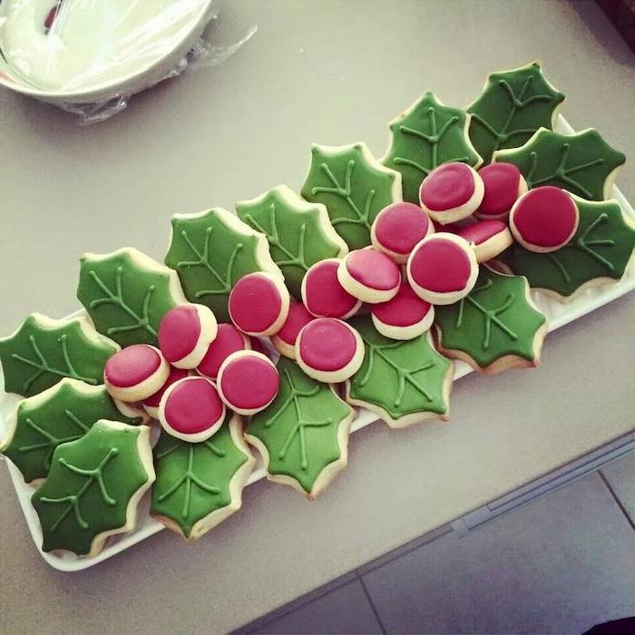 mistletoe shaped cookies, arranged on white plate, royal icing for decorating cookies, decorated with red and green icing