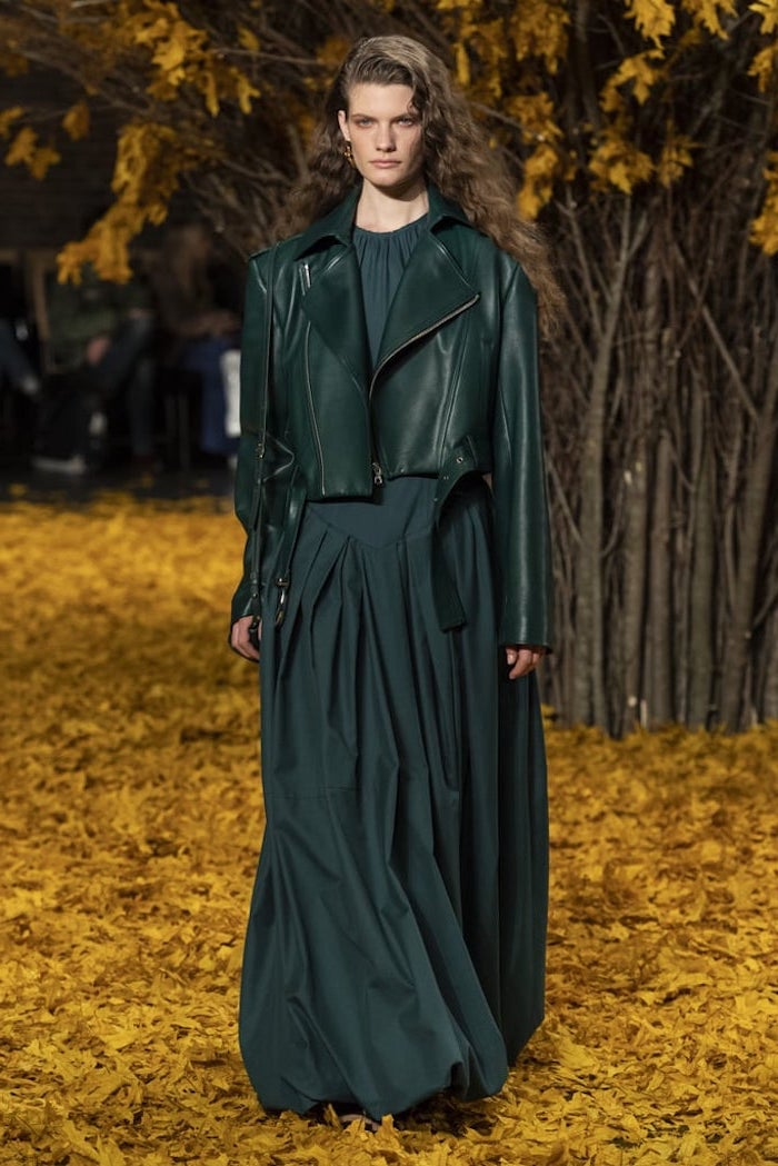 model walking down a carpet of fall leaves, wearing dark green dress, fall fashion trends, dark green leather jacket