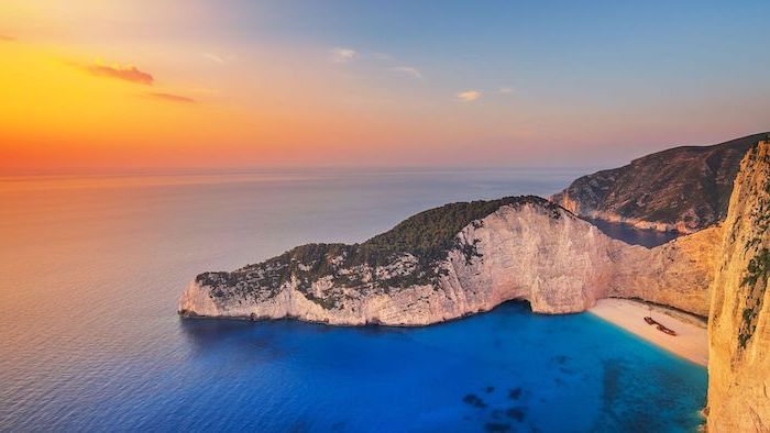 large rock going all the way into the water, beautiful beaches, navagio beach in greece, clear turquoise water