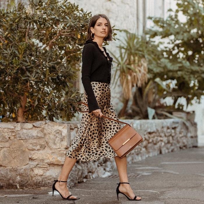 woman walking down the street, wearing silk leopard print skirt and black blouse, black sandals, winter fashion for women