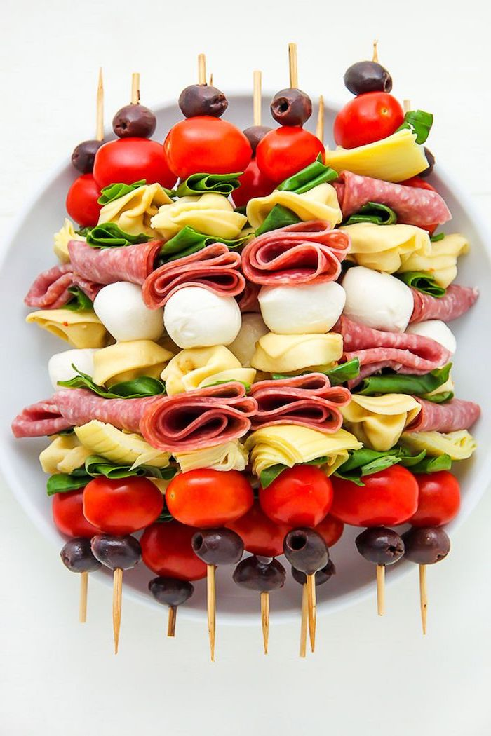 wooden skewers with meat, cheese and basil leaves, cherry tomatoes and olives, easy holiday appetizers, arranged on white plate