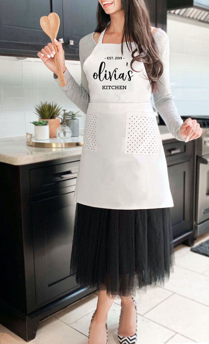olivia's kitchen personalised apron, worn by woman with black hair, christmas presents for moms, standing in the middle of a kitchen