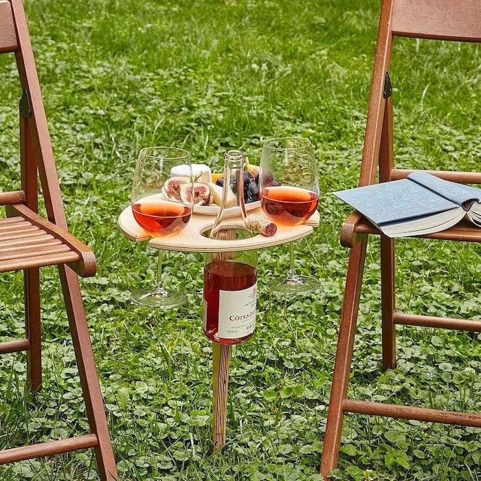 wooden wine table for outdoors, diy gifts for mom, two wooden chairs on each side, wine bottle glasses and cheese on it