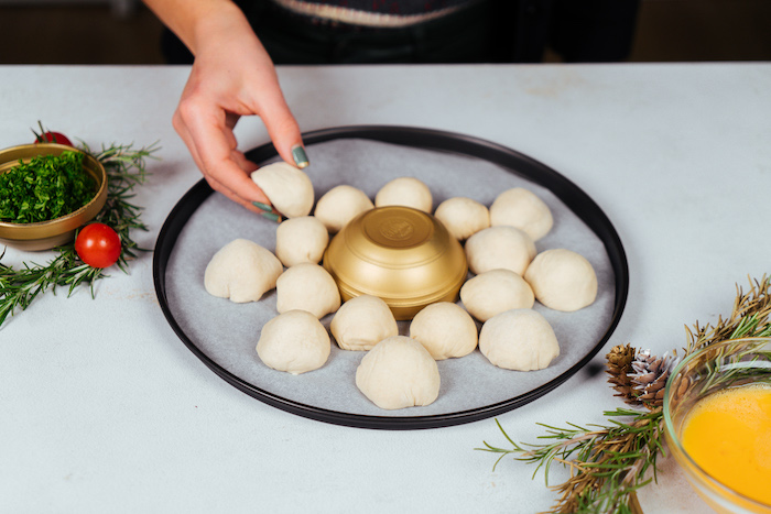 small dough balls, placed on paper lined baking sheet, pull apart christmas bread, golden bowl in the middle