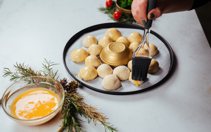 small dough balls, covered with beaten eggs, pull apart christmas bread, arranged on paper lined baking sheet