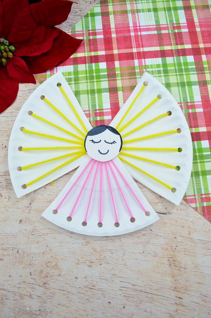 paper plate angel, made with yellow and pink yarn, diy christmas crafts, placed on a wooden surface