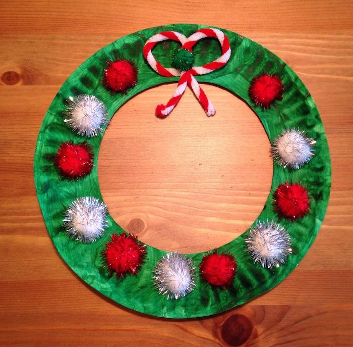 wreath made of paper plate, painted green with red and silver pompoms, diy christmas ornaments for kids, placed on wooden surface