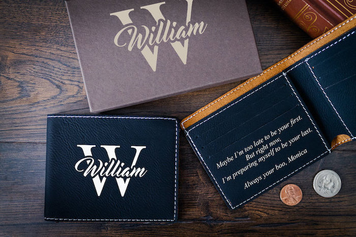 christmas gift ideas for him, personalised wallet with love message inside, made of black leather, placed on wooden surface
