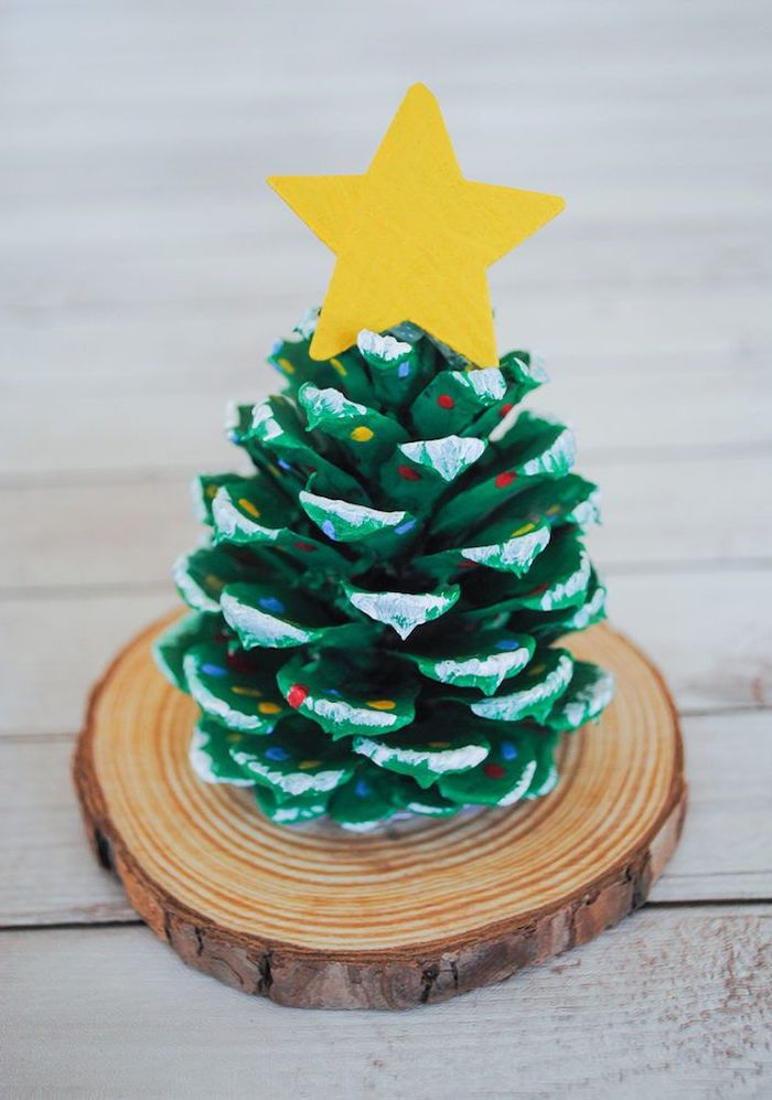 pinecone painted in green, placed on small wooden log, christmas arts and crafts, step by step diy tutorial