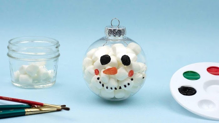 plastic bauble filled with cotton balls, diy christmas crafts, snoman face painted on it, diy christmas crafts, placed on blue surface