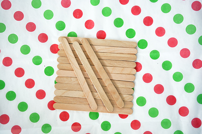 popsicle sticks, placed on white sheet with red and green dots, christmas crafts for kids, step by step diy tutorial