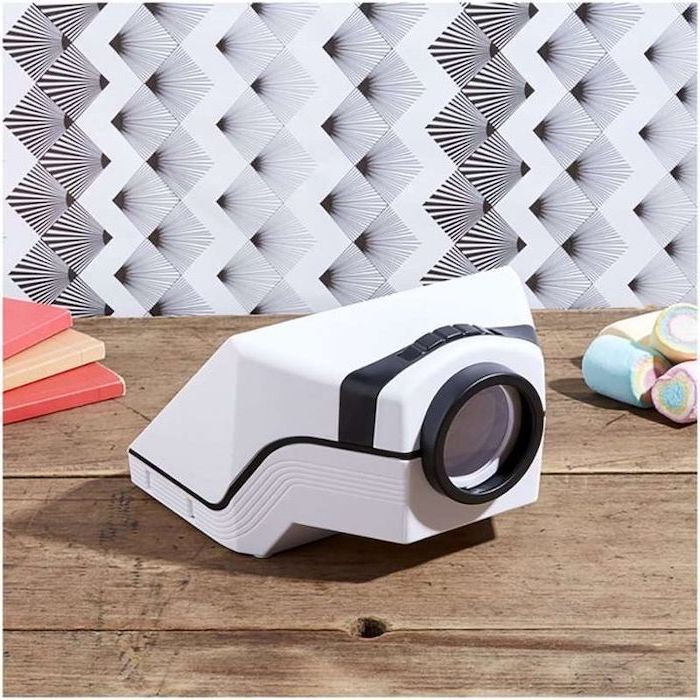 portable phone projector, placed on wooden surface, next to notebooks, creative gifts for boyfriend