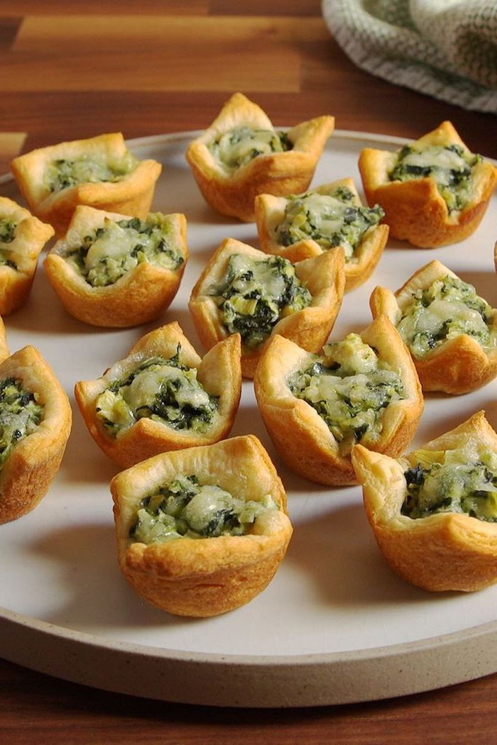 puff pastry filled with spinach and artichoke, easy holiday appetizers, arranged on white plate, placed on wooden surface