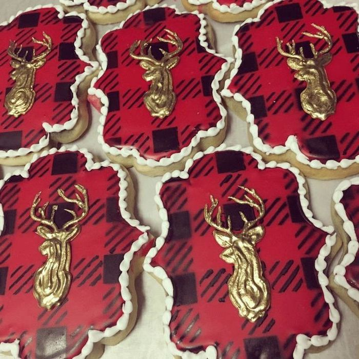 red and black checkered icing, gold deer decoration on top of cookies, royal icing for decorating cookies, placed on white surface