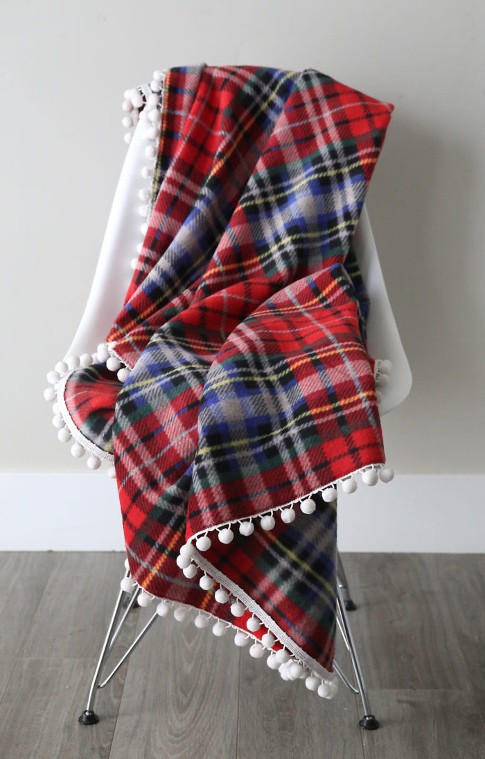 red flannel fleece blanket, spread out on white chair, placed on a wooden floor, christmas presents for moms