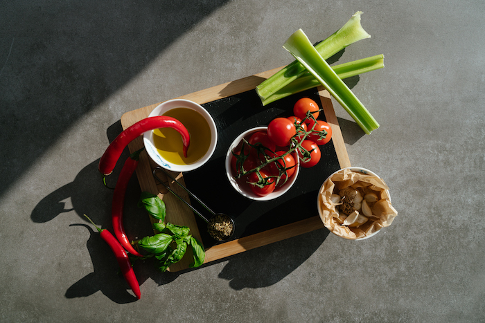 chilli peppers and tomatoes, celery and garlic, arranged on wooden cutting board, tomato soup, grey countertop