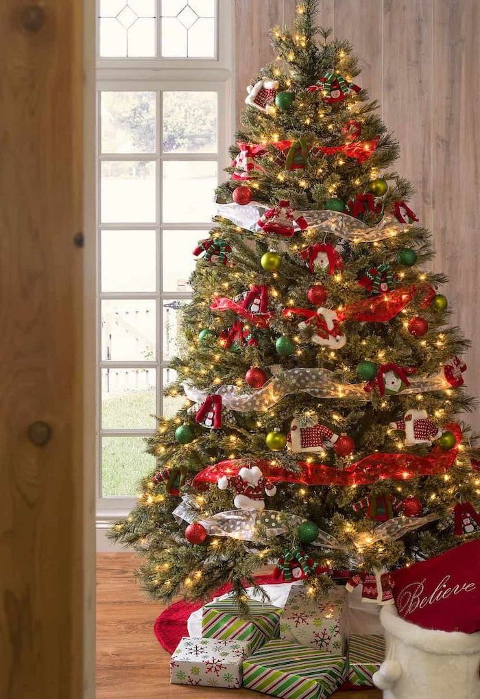 gold ribbon wrapped around a tree, decorated with green and red ornaments, elegant christmas tree decorating ideas