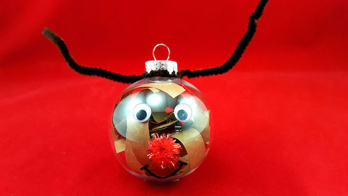 plastic bauble filled with paper, christmas ornament crafts, turned into a reindeer, placed on red surface