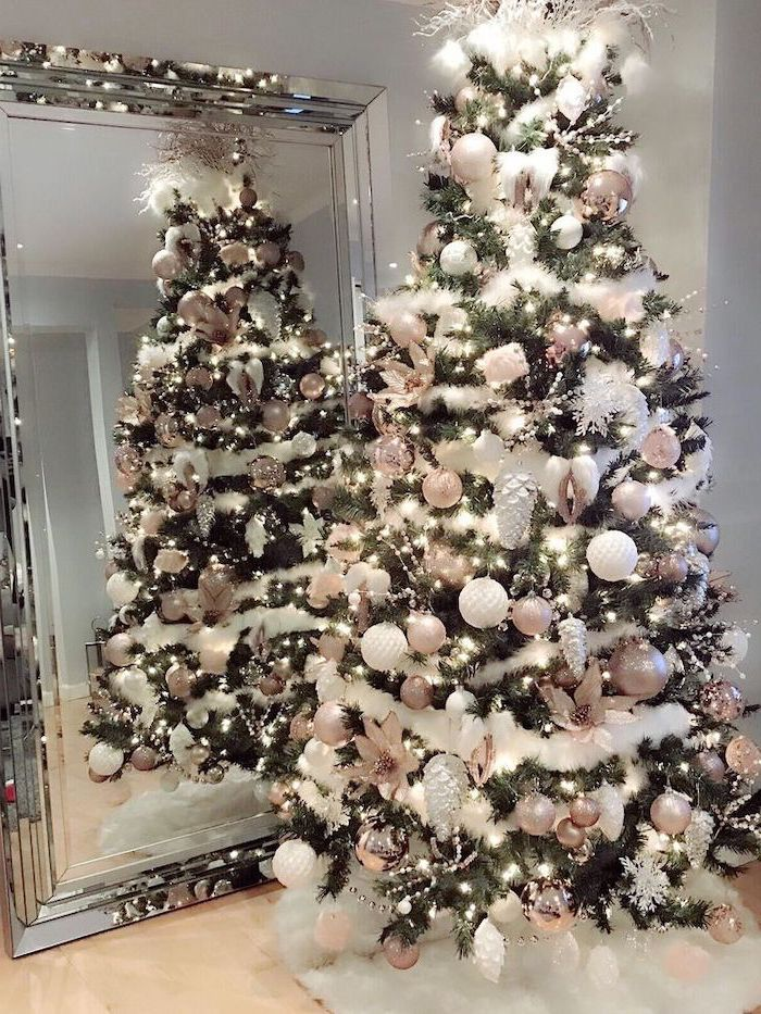 white garland wrapped around a tree, rose gold and white ornaments, elegant christmas tree decorating ideas, placed in front of a mirror on white rug