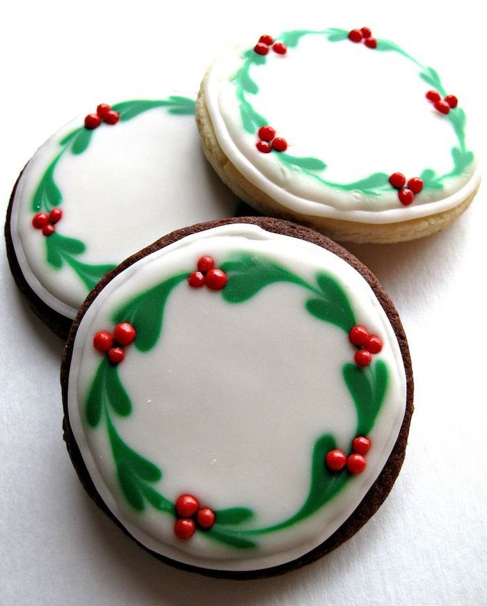 round cookies with wreaths drawn on them, using white and green icing, christmas cookie icing, placed on white surface