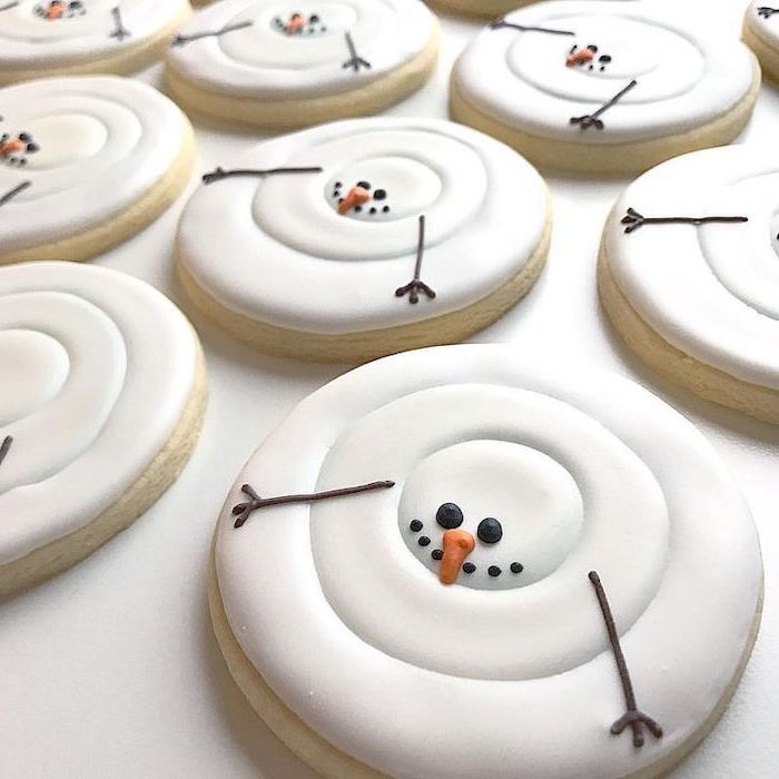 royal icing christmas cookies, round cookies with marshmallow fluff on top, shaped as snowmen, placed on white surface